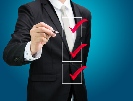 businessman checking mark checklist marker Isolated on blue background Banque d'images