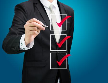 businessman checking mark checklist marker Isolated on blue background Standard-Bild