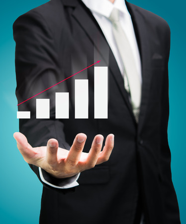 businessman standing: Businessman standing posture hand holding graph finance isolated on over blue background Stock Photo