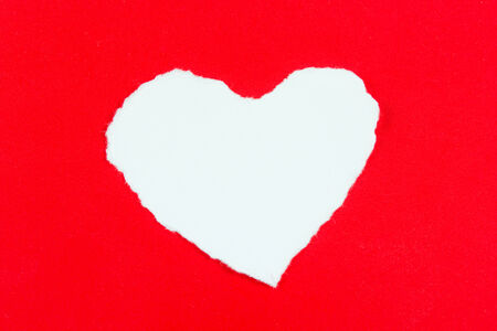 Heart shaped rip paper white on over red background photo