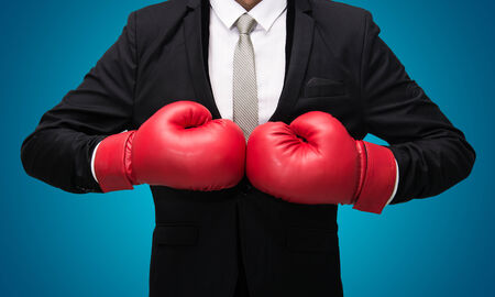 boxing ring: Businessman standing posture in boxing gloves isolated on over blue background