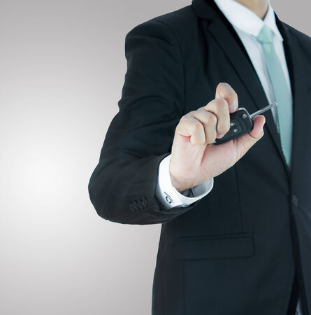 Businessman standing posture hand key for car isolated on over gray background photo