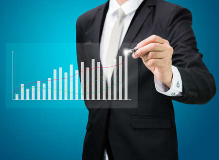 Businessman hand drawing a graph Isolated on blue background photo