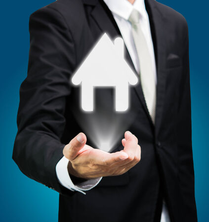 Businessman standing posture hand holding house icon isolated  photo
