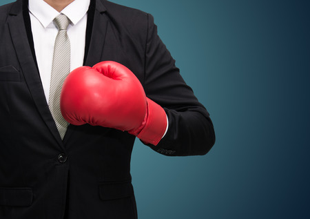 Businessman standing posture in boxing gloves isolated on over blue background photo