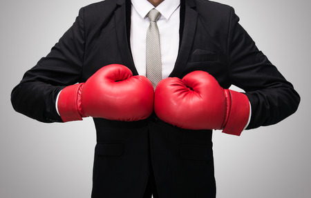 Businessman standing posture in boxing gloves isolated on over gray background photo