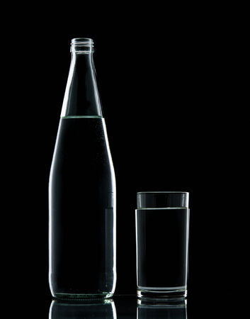 Bottle and Glass water clear isolate on over black background photo