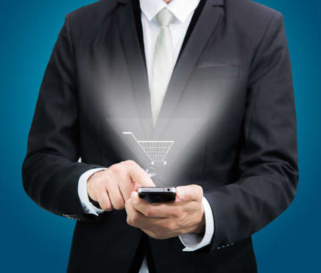 Businessman standing posture hand hold mobile phone isolated on blue background photo