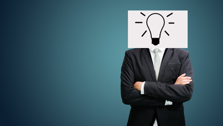 Businessman standing white paper ideas face holding front of head on dark background photo
