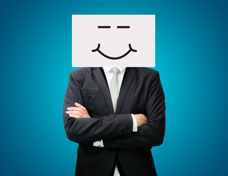 Businessman standing white paper happy smile face holding front of head on blue background photo