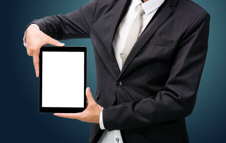 Businessman standing posture hand holding blank tablet isolated on dark background photo