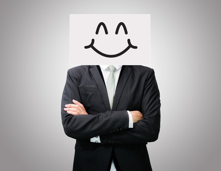 Businessman standing white paper happy smile face holding front of head on gray background photo