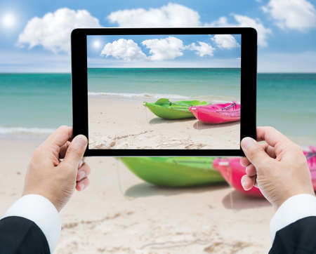 Businessman hands tablet taking pictures canoe on beach and sea photo