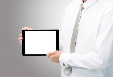 Businessman standing posture hand holding blank tablet isolated on over gray background photo