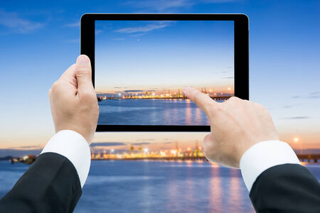 commercial docks: Businessman hands tablet taking pictures Commercial docks at sunset with ship and cranes
