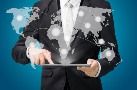 Businessman standing posture hand hold globe map on tablet isolated on blue background Stock Photo