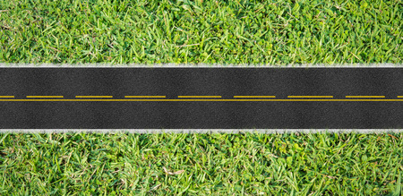Top view asphalt road on the green grass photo