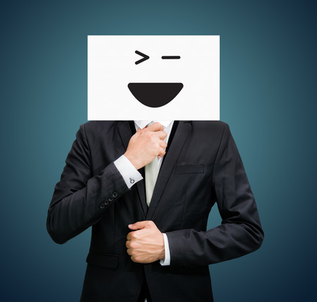 Businessman standing white paper happy smile face holding front of head on dark  photo