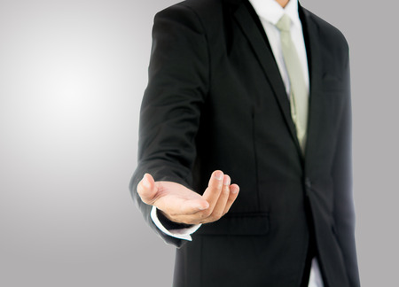 Businessman standing posture show hand isolated on over gray  Stockfoto