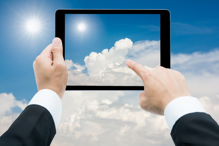 multitouch: Businessman hands tablet taking pictures The sun and white clouds background on blue sky Stock Photo