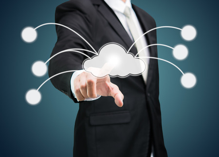 Businessman hand pressing cloud icon on concept for cloud computing on drak background photo