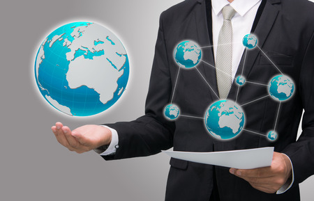 Businessman standing posture hand holding Earth icon isolated on gray background photo