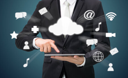 Businessman hand holding tablet cloud connectivity on drak background photo