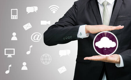Businessman holding cloud computing network on gray background photo