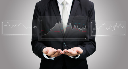 Businessman standing posture hand holding graph finance isolated on over gray background photo