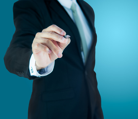 Businessman standing posture hand hold a pen isolated on over blue background Stockfoto