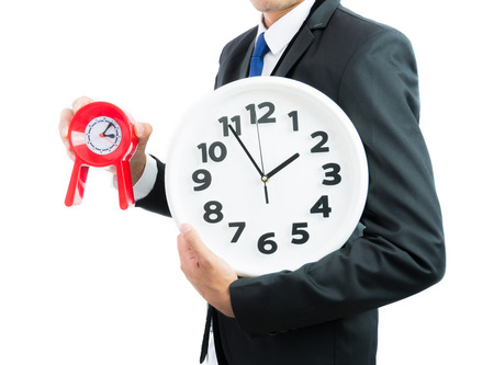 Red and white clock holding in businessman hands isolated on over white background photo