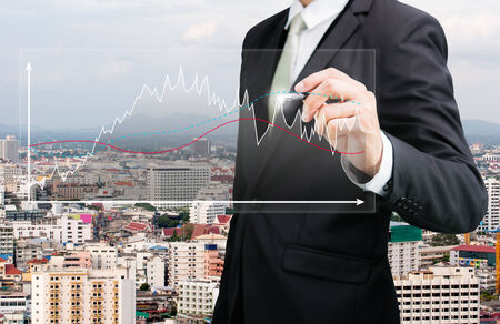 Businessman standing posture hand hold a pen on City  background photo