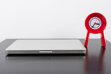 economic botany: Laptop and red clock  on black wooden table on wall background