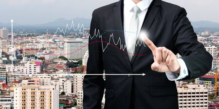 Businessman standing posture hand touch graph finance on City background photo