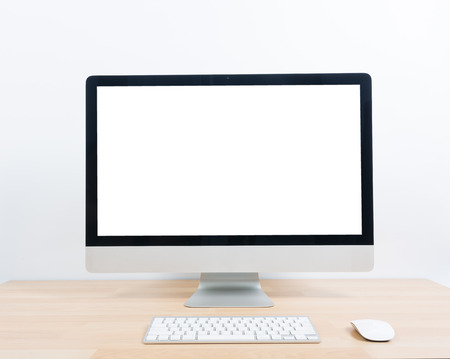 Office monitor computer, mouse on wooden table and white wall background