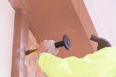 demolishing: Construction worker demolishing old brick wall with chisel tool Stock Photo