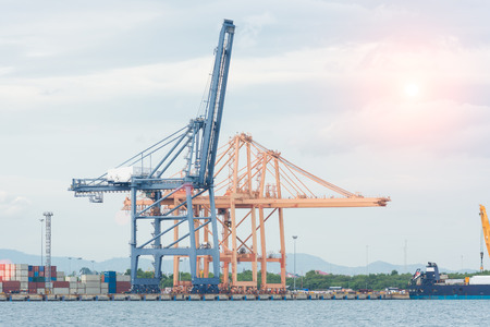 world economy: Industrial Container Cargo freight ship with working crane bridge Stock Photo