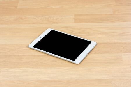 White digital tablet on wooden table background