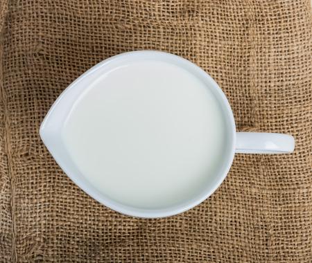 Leche de vaca y una jarra de cerámica de mesa de madera Foto de archivo - 44253492