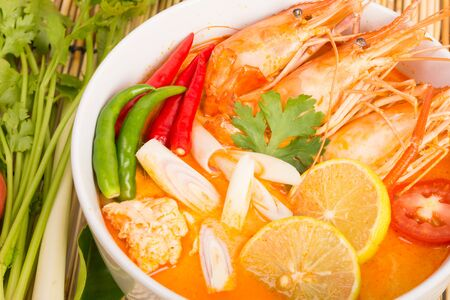 seafood soup: Tom Yum Goong, Thai hot spicy soup shrimp on wooden background, Thailand Food