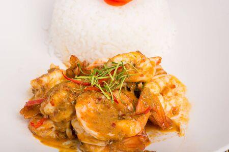 camaron: Curry camarones fritos y arroz cocido en un plato blanco close-up en la mesa con el fondo de madera