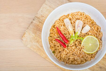 instant noodle: Hot and spicy instant noodle on wooden background Stock Photo
