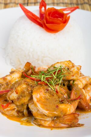 cooked rice: Curry fried shrimps and cooked rice in white dish closeup on table with wooden background Stock Photo