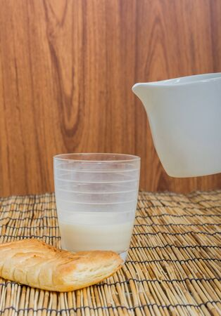 lactation: Milk from ceramic jug pouring into glass on wooden table background Stock Photo
