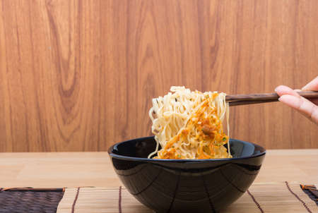 cooked instant noodle: Hot and spicy lap instant noodle in black cup on wooden background Stock Photo