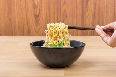 Hot and spicy lap instant noodle on wooden background