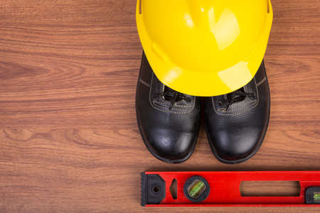 sued: Top view safety shoes and composition of working tools on wooden table