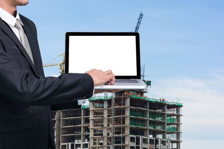 coordinating: Engineering working hold conputer notebook in front of construction supervisor site Stock Photo