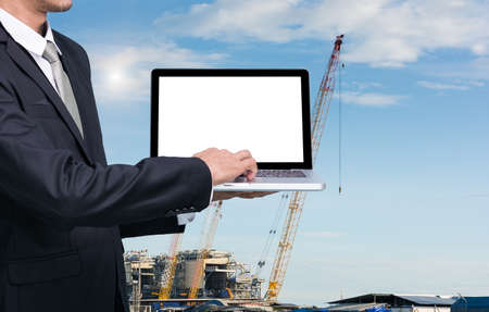 Engineering working hold conputer notebook in front of construction supervisor site Stock Photo