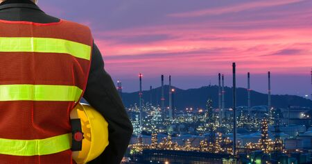 electrical contractor: Hand or arm of engineer hold yellow plastic helmet in front of oil refinery industry Stock Photo